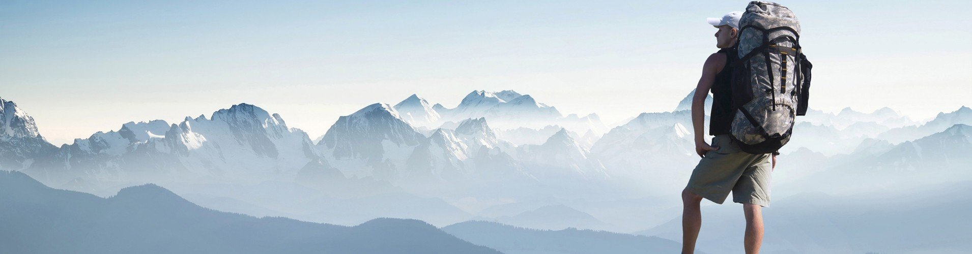 Bergsteiger mit Rucksack auf einem Plateau blickt auf schneebedeckte Gipfel