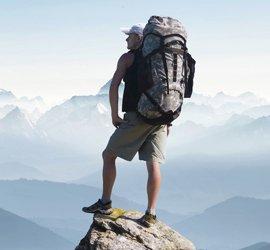 Bergsteiger mit großem Rucksack steht auf Felsvorsprung und blickt in die Ferne. Im Hintergrund ragen schneebedeckte Gipfel aus dem Nebel.