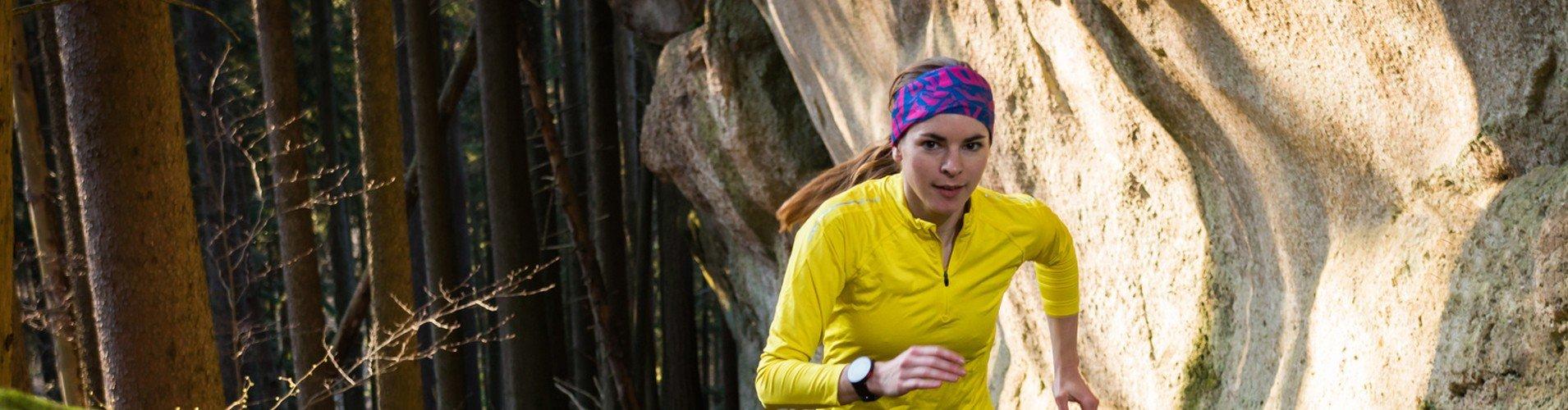 Joggende Frau im Wald vor einer Felswand
