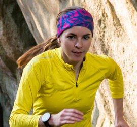 Joggende Frau mit Stirnband vor einer Felswand